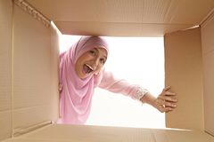 Relocation. Woman opening a carton box and looking inside, relocation and unpacking concept Royalty Free Stock Photo