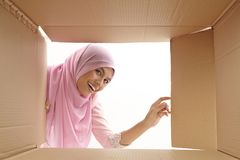 Relocation. Woman opening a carton box and looking inside, relocation and unpacking concept Stock Photos