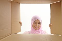 Relocation. Woman opening a carton box and looking inside, relocation and unpacking concept Royalty Free Stock Photography