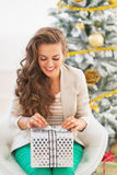 Woman opening christmas present box in front of christmas tree Royalty Free Stock Photography