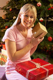 Woman Opening Christmas Present In Front Of Tree Royalty Free Stock Photography