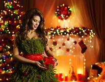 Woman Opening Christmas Present Gift, Fashion Model Xmas Tree Dress. Woman Opening Christmas Present, Model in Xmas Tree Dress Open Gift Box, Decorated New Year stock image