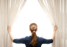 Woman opening curtains Stock Image