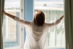 Woman opening curtains stock photos