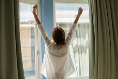Woman opening curtains. In the bedroom in the morning royalty free stock photography