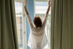 Woman opening curtains royalty free stock images