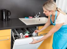 Woman opening dishwasher Stock Images