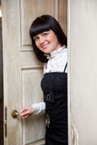 Woman opening a door Stock Images