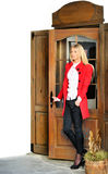 Woman opening a door. Woman in red suit opening a door stock photography