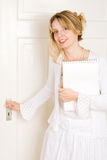 A woman opening a door. A woman with a note pad opening a door Stock Image