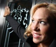 Woman opening the door Stock Photos