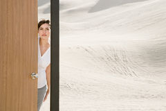 Woman opening door in desert Royalty Free Stock Photography