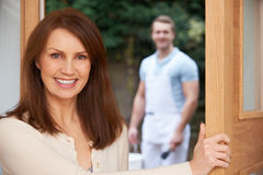 Woman Opening Door To Decorator Royalty Free Stock Images