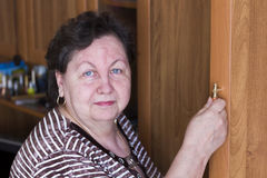 The woman,opening the door wall Cabinet Stock Images