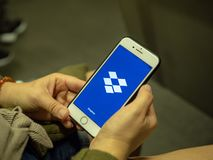Woman opening Dropbox mobile app with logo on iPhone screen while commuting on subway train stock image