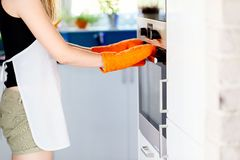 Woman opening electric oven Royalty Free Stock Photo
