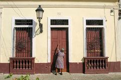 Woman opening the entrence door of her colonial house Royalty Free Stock Photos