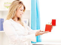 Woman opening fancy box at home. Blond woman opening fancy box at home Royalty Free Stock Images