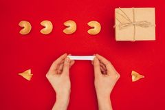 Woman opening fortune cookie over red surface, Chinese New Year concept royalty free stock photography