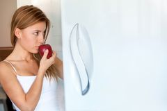 Woman opening the fridge with an apple Stock Images