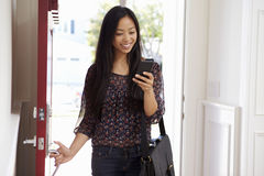 Woman Opening Front Door Whilst Checking Mobile Phone Stock Photography