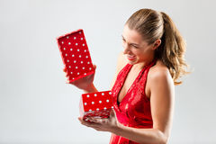 Woman opening the gift and is happy Royalty Free Stock Images