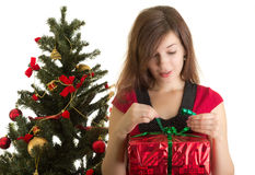 Woman opening gift near Christmas tree Royalty Free Stock Photography