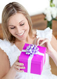 Woman opening a gift sitting on the floor royalty free stock photos