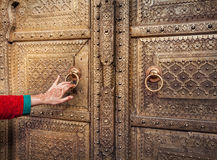 Woman opening golden door in Jaipur Royalty Free Stock Photo