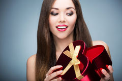 Woman opening heart shaped box Stock Photography
