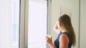 Woman opening her bedroom curtains and drinking orange juice in slow motion stock video footage