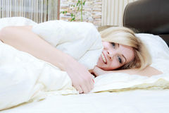 Woman opening her eyes in her bedroom Royalty Free Stock Image