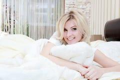 Woman opening her eyes in her bedroom Stock Photos