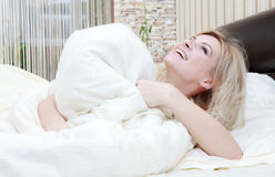 Woman opening her eyes in her bedroom Stock Photography