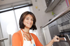 Woman opening the kitchen oven Royalty Free Stock Photos