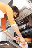 Woman opening the kitchen oven Stock Photo
