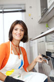 Woman opening the kitchen oven Stock Image