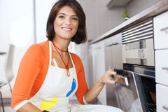 Woman opening the kitchen oven Royalty Free Stock Photography