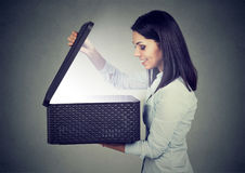 Woman opening looking into gift box with bright light coming out. Happy woman opening looking into gift box with bright light coming out Royalty Free Stock Photos
