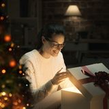 Woman opening a magical Christmas gift stock photos
