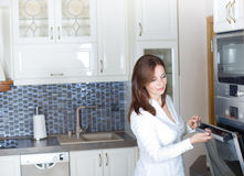 Woman opening oven door Royalty Free Stock Photos