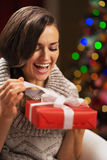 Woman opening present box in front of christmas lights Stock Photos