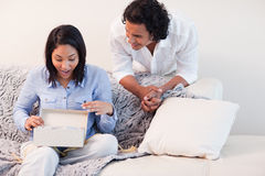 Woman opening the present she got from her boyfriend Royalty Free Stock Image