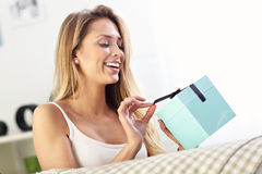 Woman opening present on sofa Royalty Free Stock Photos