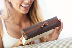 Woman opening present on sofa. Picture showing woman opening present on sofa Stock Photo