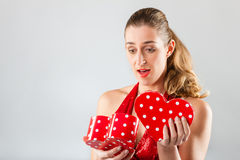 Woman opening present for valentines day. Woman opening heart shaped gift box with present for birthday or valentines day stock image
