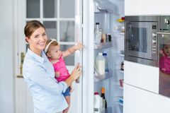 Woman opening refrigerator while carrying baby girl Stock Images