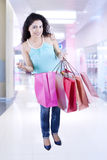 Woman opening shopping bags in the mall Royalty Free Stock Photography