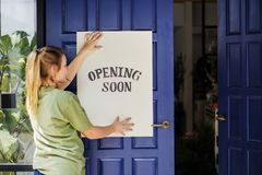Woman with a opening soon signage Stock Photography