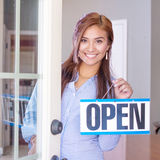 Woman Opening A Store. Woman opening her store with an open sign Stock Photos